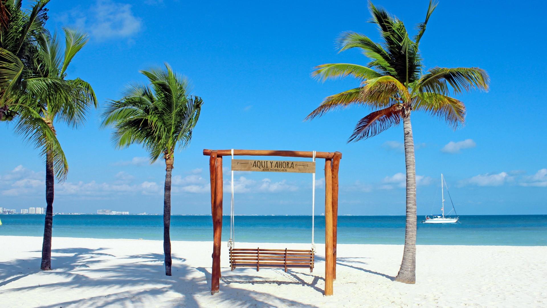 Columpio de madera sobre la arena con vista al mar