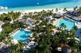 Toma panorámica de hotel sobre playa con dos albercas