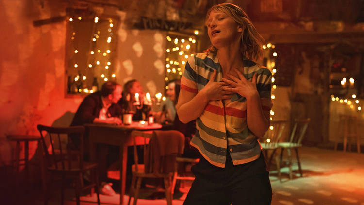 Mia Wasikowska in a stripy top dancing in a bar with fairy lights and bathed in red light