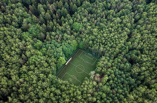 Aerial shot of a green football pitch completely surrounded by dense, tall green trees