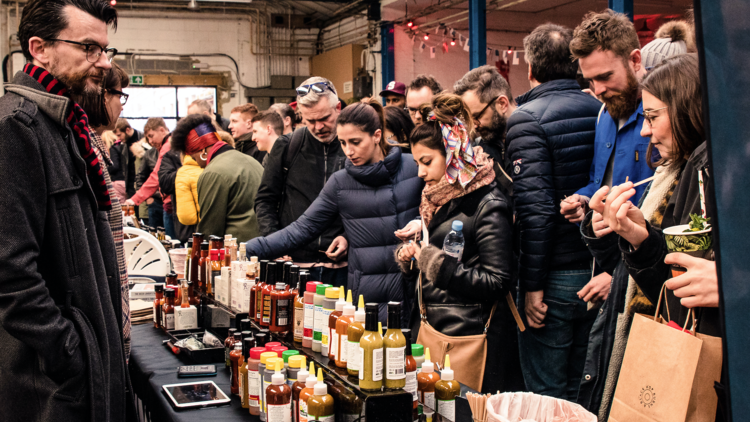 people looking at a hot sauce stall