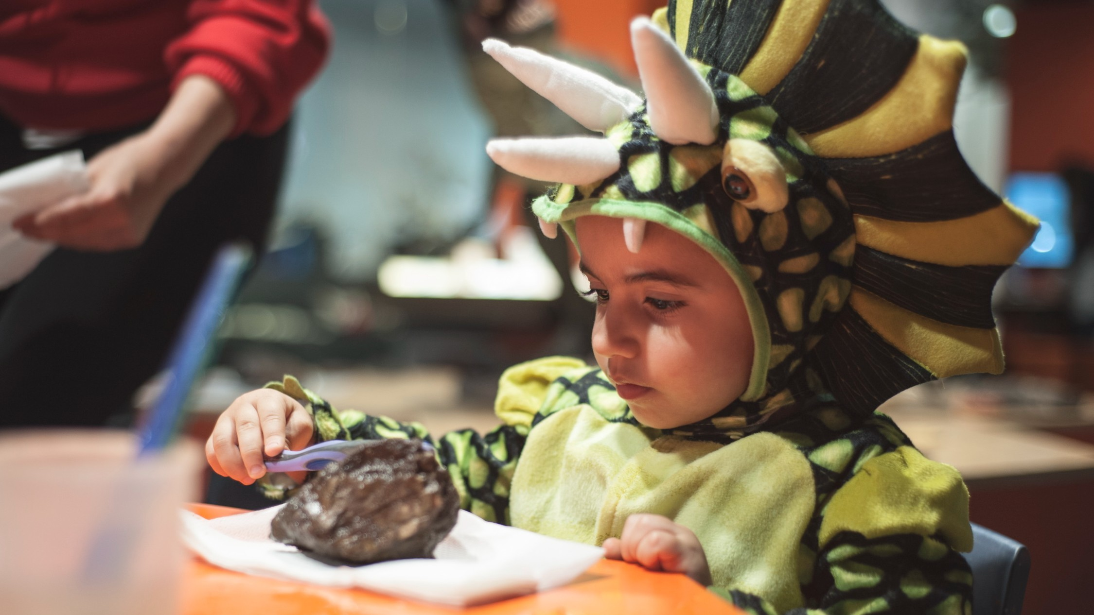 A kid in a dinosaur outfit