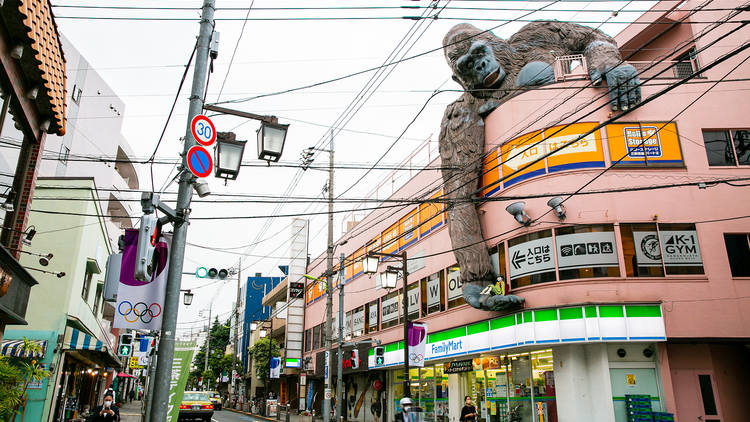 A three-storey commercial building with a large gorilla statue on top