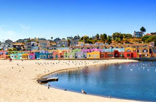 Sandy beach with multicoloured beach huts on a sunny day in Santa Cruz, CA