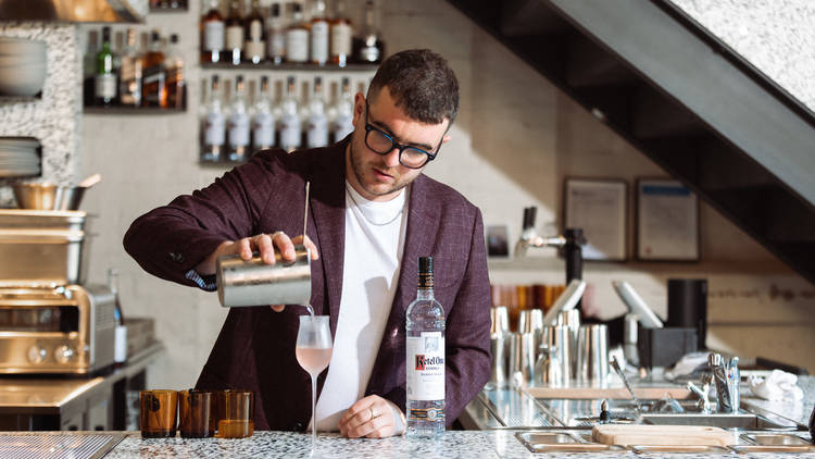 Evan is seen straining a cocktail into a tulip glass with a bottle of Ketel One vodka to his right