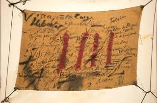 Inscripcions i quatre barres damunt arpillera