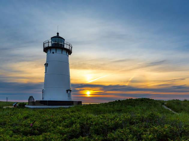 Sun rising over the circular white building of Edgartown Lighthouse, Martha's Vineyard
