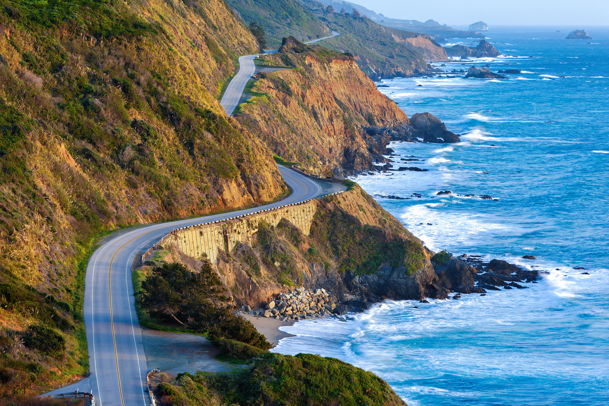 Winding road along the edge of cliffs justting out into the sea on the Pacific Coast Highway