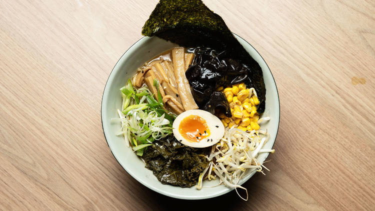A bowl of ramen with soft egg, nori and garnishes on a wooden table