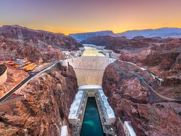 Aerial shot of the concrete wall of the Hoover Dam at sunset