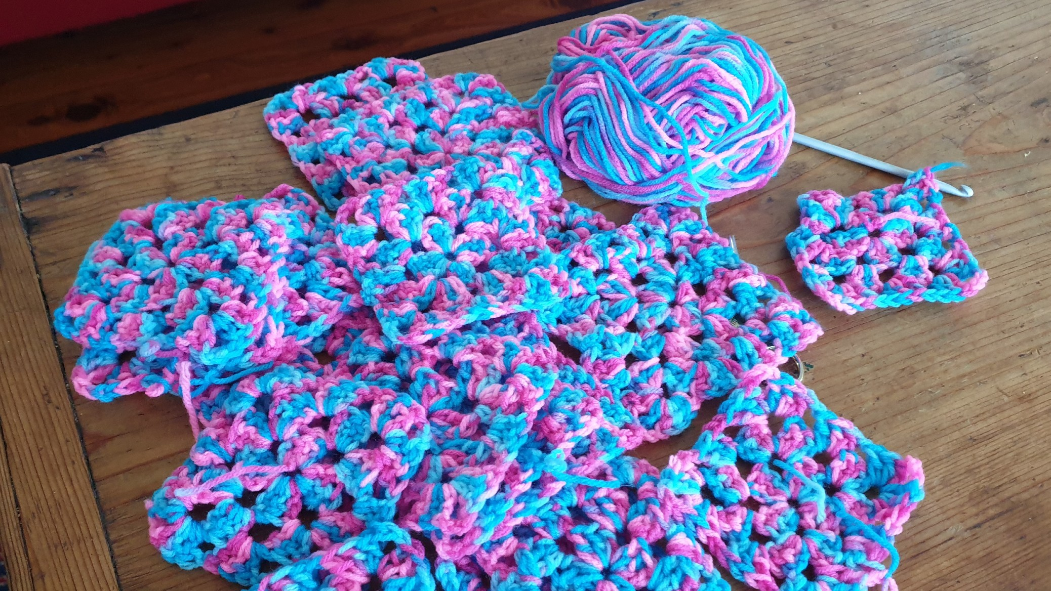 A ball of wool sits next to a pile of crochet granny squares and a crochet hook.