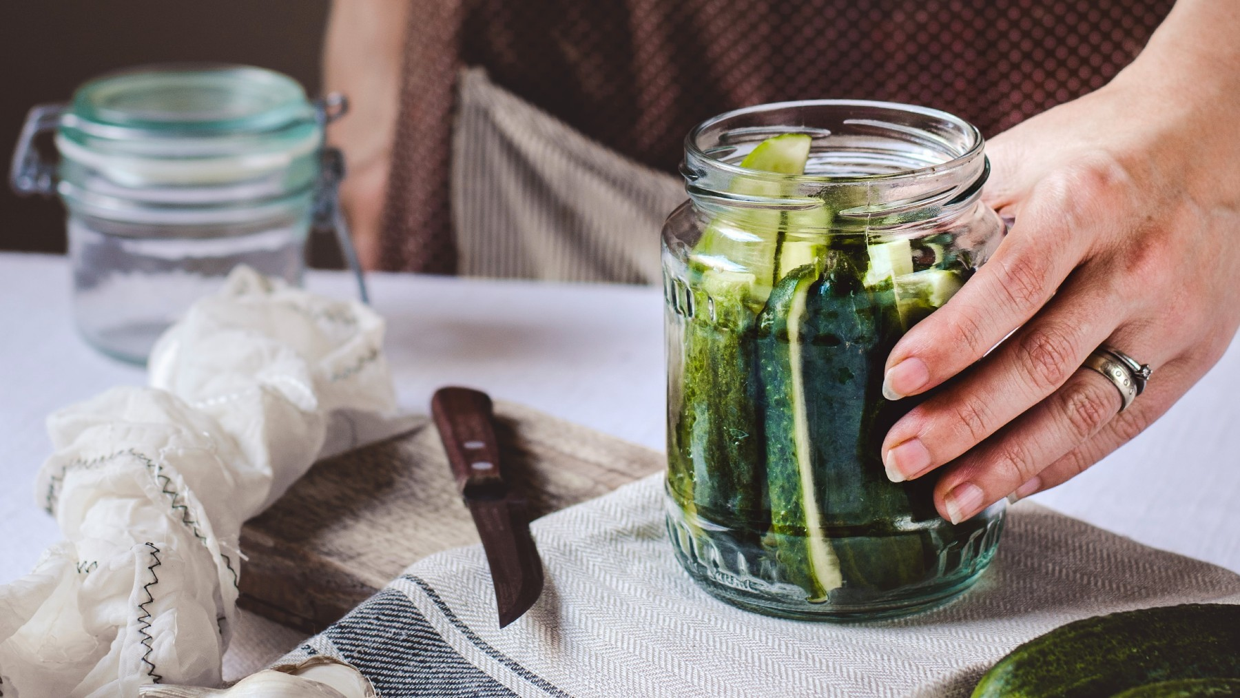 Close up of person making pickles in a jar.