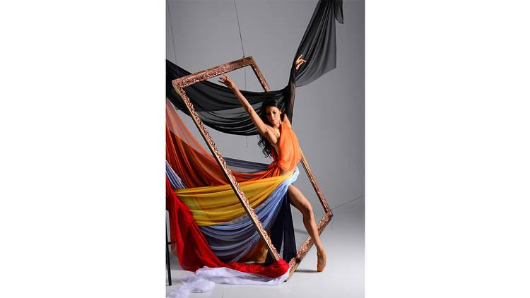 Elisa Carrillo posando en pose de ballet con un cuadro y un vestido colorido