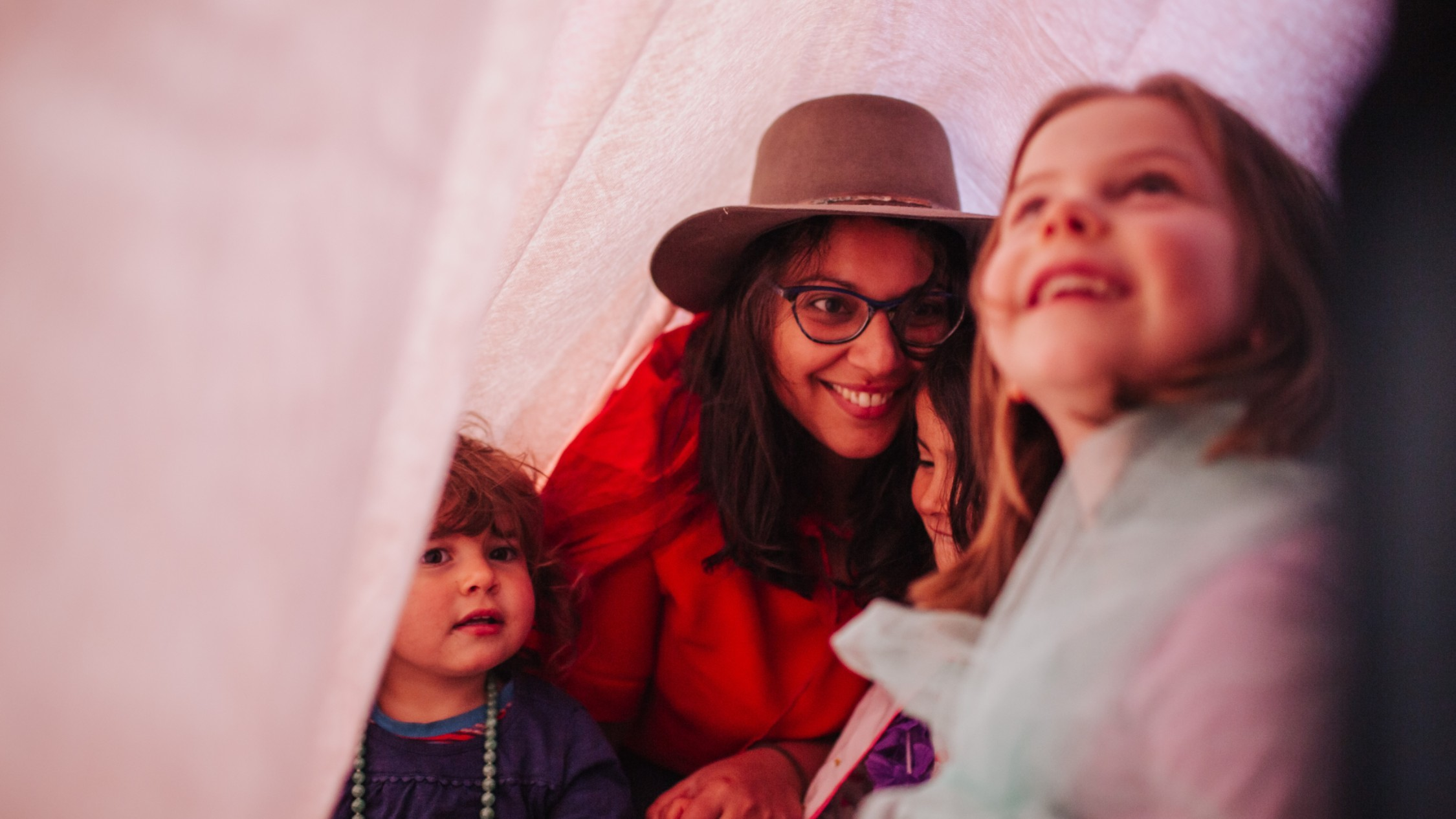 A family hide and play under a bedsheet