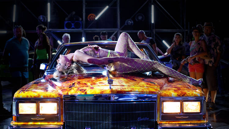 A blone woman in a corset and suspenders lies on the bonnet of a racer car with fire painted on it