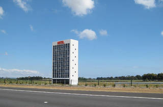 A generic white office building on the side of the road. It has 'hotel' written in red block letters at the top of the building