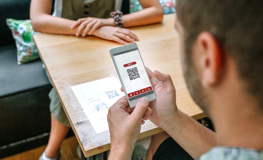 Un home escanea un código QR en un restaurante