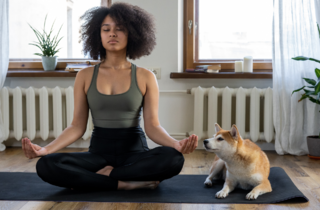 Woman meditating with her dog.