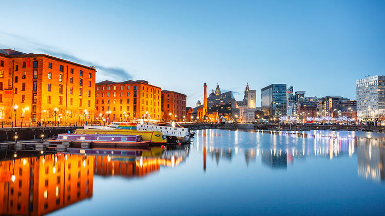 Sunet over Liverpool docks, with the illuminated buildings on the waterfront reflected in the water