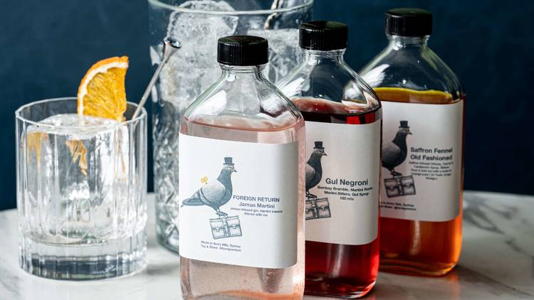 three bottles of Foreign Return cocktails with pigeons on them and a rocks glass with ice cubes