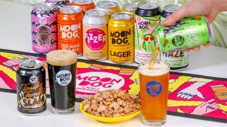 A selection of brightly coloured beer cans plus some glasses filled with a dark beer and a pale ale. There is also a piled plate of peanuts