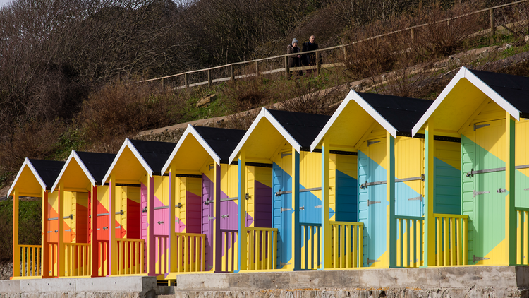 A row of beach huts mostly painted yellow, with multicoloured triangles on the face of each hut