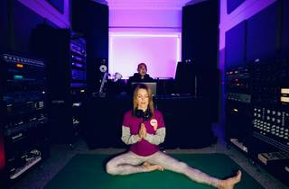 Angel sits on yoga mat with hands in prayer position, she is in a music studio