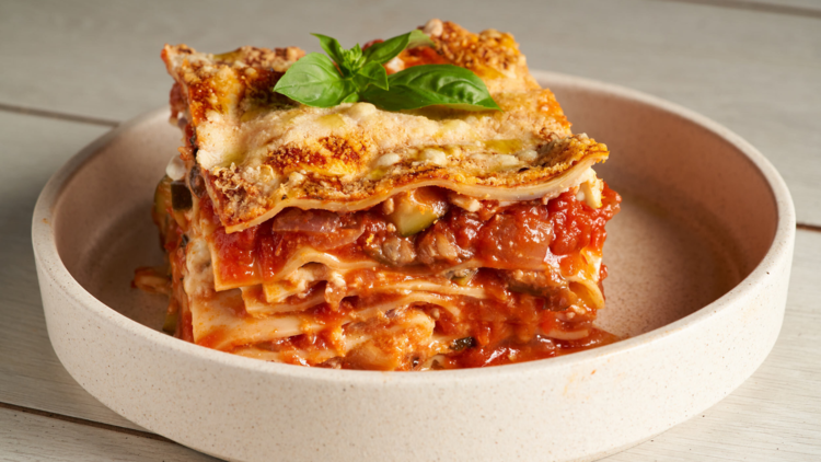 A square of lasagne sits in a round high lipped bowl on a white table
