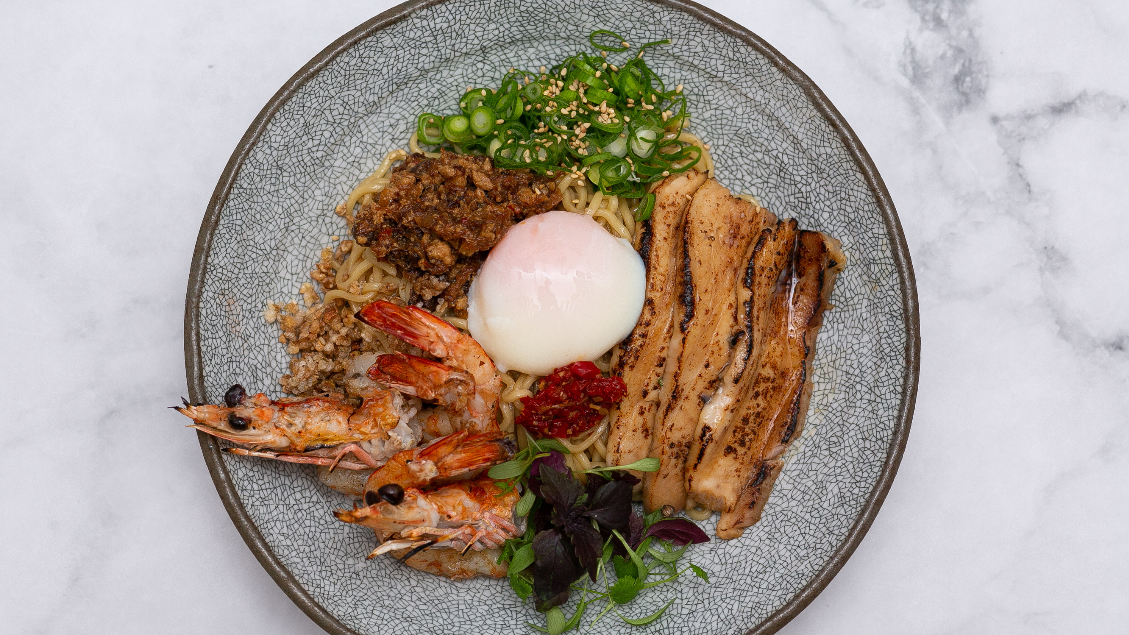 A don bowl with pork belly, fried prawns and a poached egg