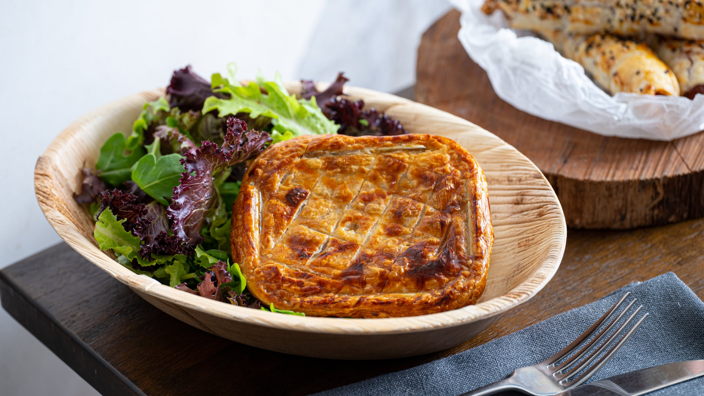 Pie and salad in a wooden bowl with cutlery in the foreground