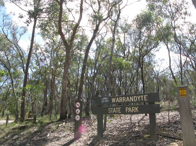 """Bushland with a wooden sign saying 'Warrandyte State park"""""""