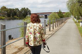 A woman wearing a floral patterned jacket with dyed red hair and carrying a camera walks along a river. A bridge is in the background