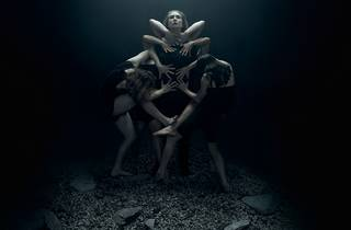 A woman stands with her head upturned in a dark room. A soft white light illuminates her and shows three dancers crowding around her, their arms bent at weird angles to touch her