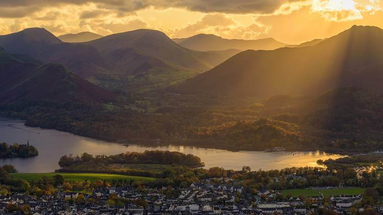 Sunrise over the hills behind Derwentwater lake and the neighbouring town of Keswick