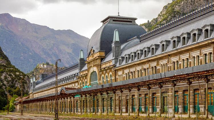 The front of Canfranc Station in the Pyrenees, with mountains in the background