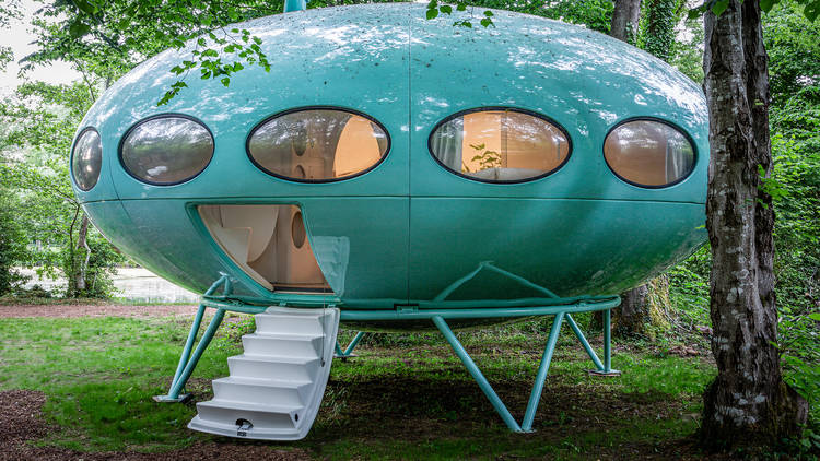The Future House, a bright blue round UFO-like pod raised up on stilts, with round windows looking in to the bedroom inside