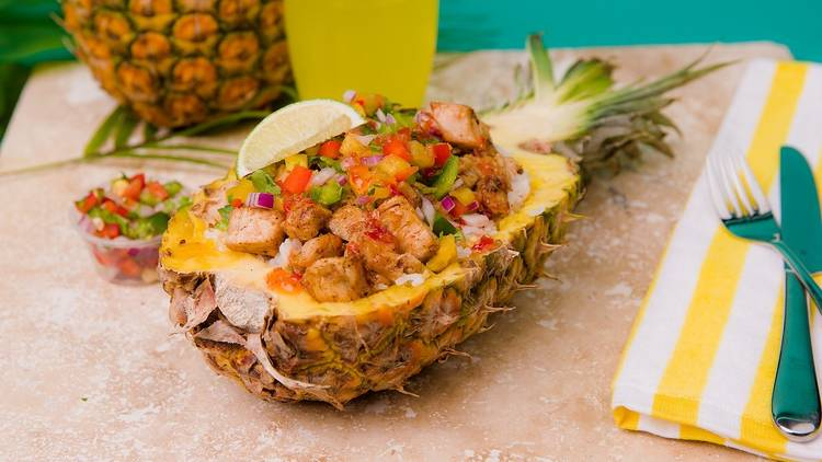 Meat and vegetables laid inside a hollowed out pineapple