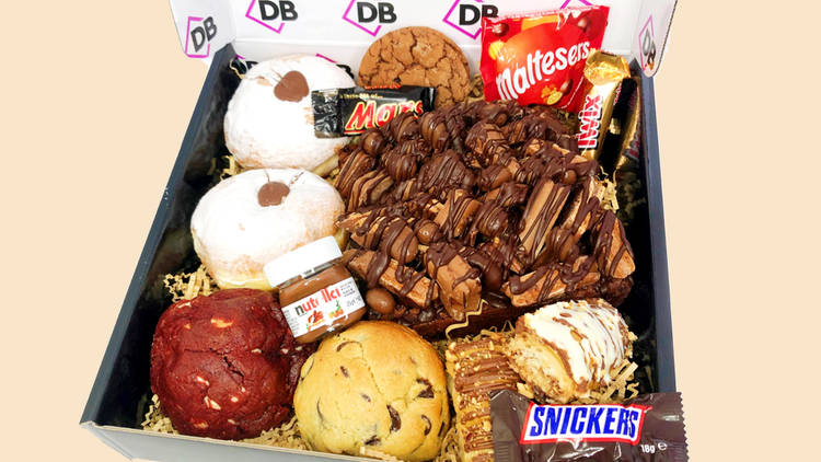 A box with doughnuts, Nutella, Snickers, cookies, a giant brownie slab and more.