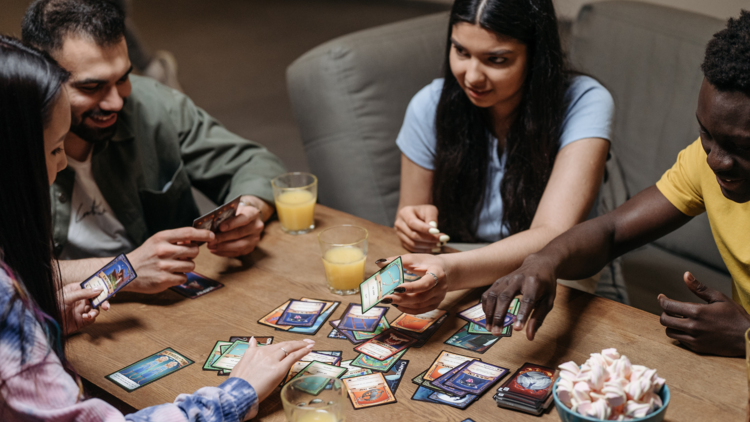 Four friends gathered around a table playing a card-based board game.
