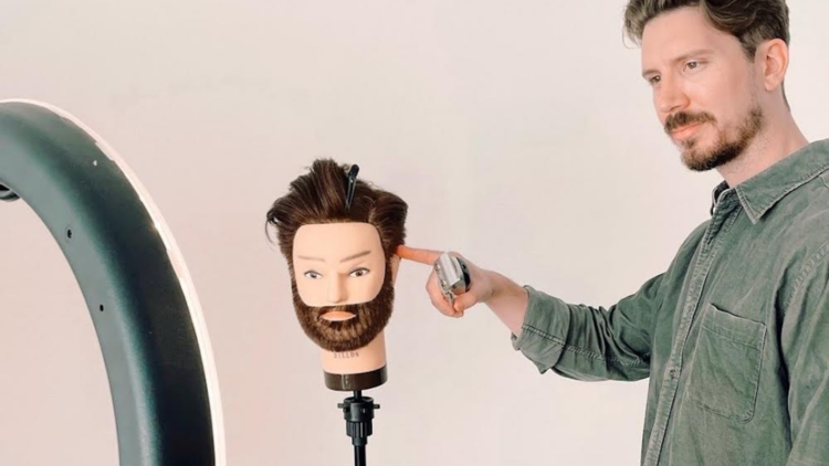 Barber Nic Singer demonstrates how to give a home haircut, he is holding an electric razor and pointing at a dummy head with beard.