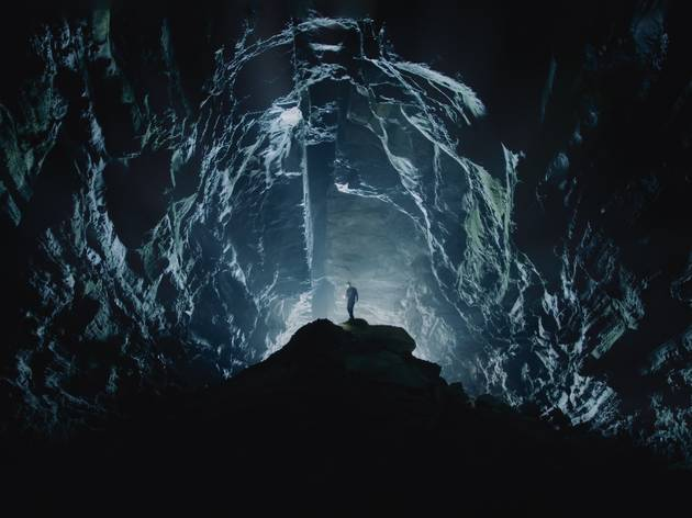 A stunning shot of a man in the distance in an underground cave that's lit up eerily blue