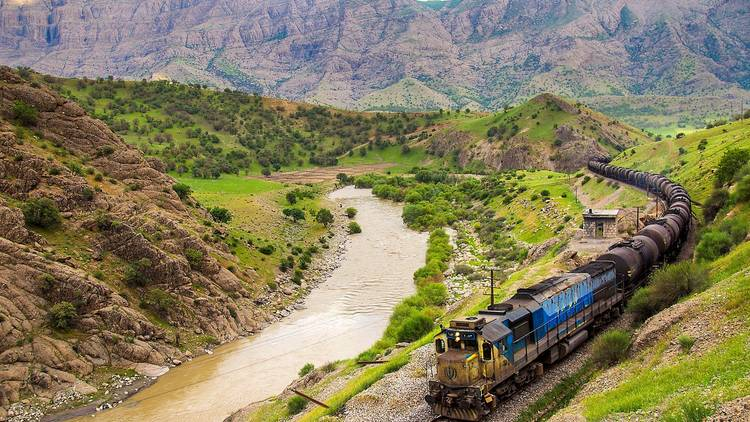 A train travels on a track passing a brown river with greenery and mountains in the background