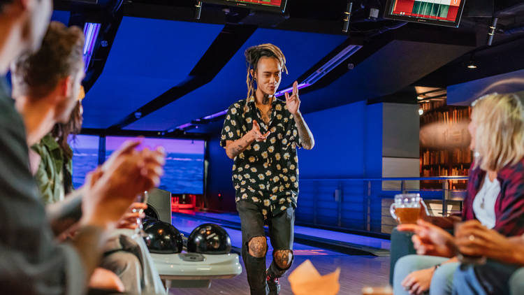 A man stands in front of a bowling alley with his group of friends