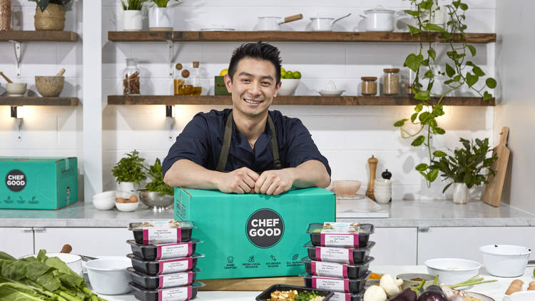 Reynold from Masterchef leans on a Chefgood box surrounded by fresh vegetables and packaged meals
