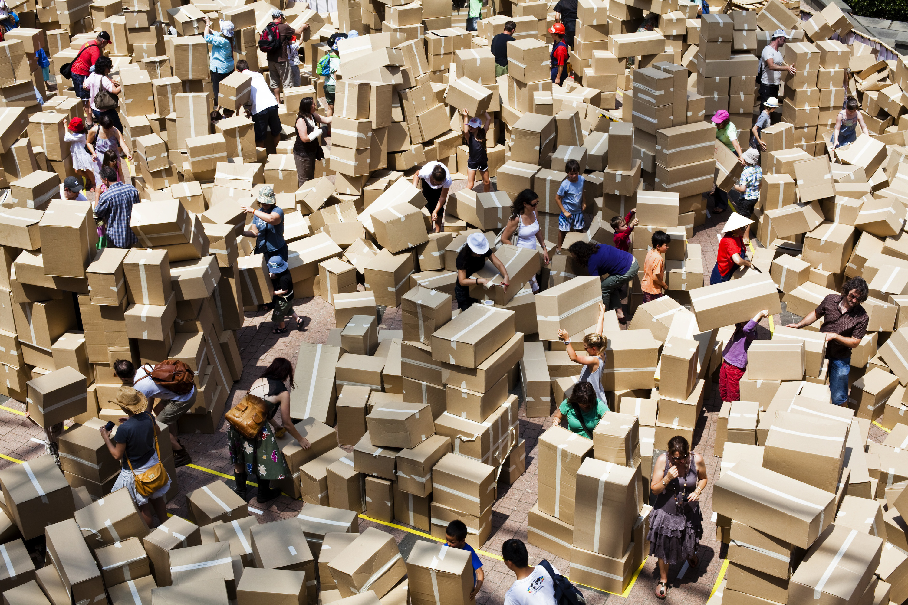 A lot of cardboard boxes with people building towers out of them