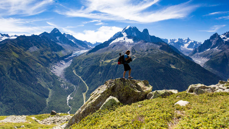 Hiker on top of a rock overlooking mountains with greenery and valleys