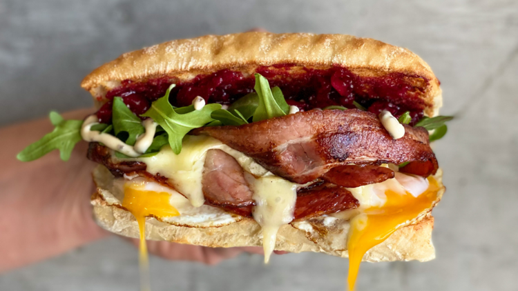 A bacon and egg roll with beetroot relish and rocket