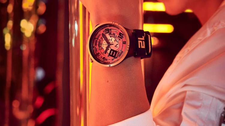 The bright orange Oops! Swatch watch shown on an arm with the person's face seen smiling in the back of the frame. Orange neon lights and reflective surfaces can be seen in the background.