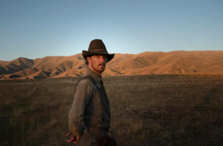 Benedict Cumberbatch in a cowboy hat in a Wild West setting with scrub and sandy hills
