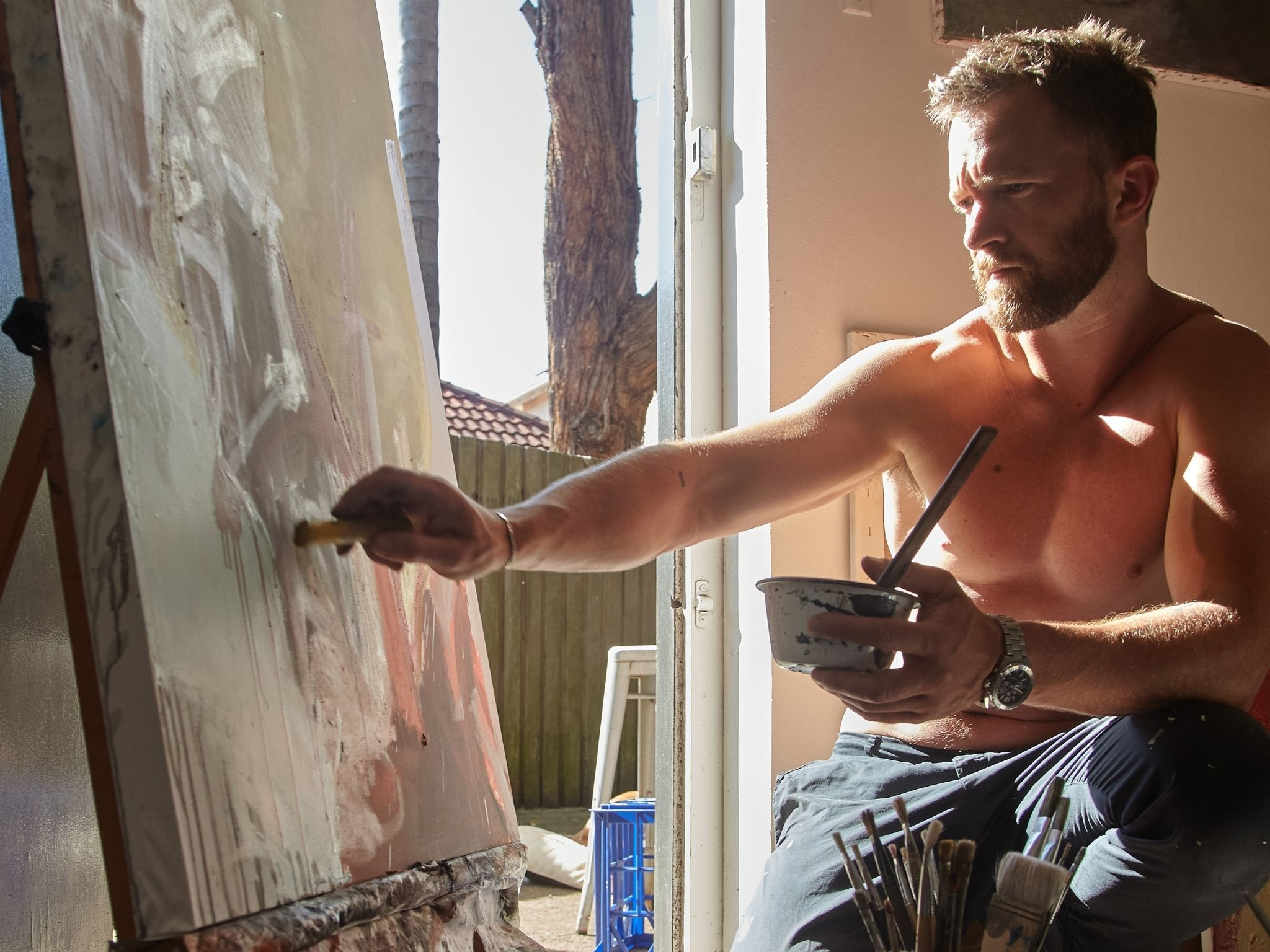 Actor Tim Draxl sitting at an easel painting, bare chested